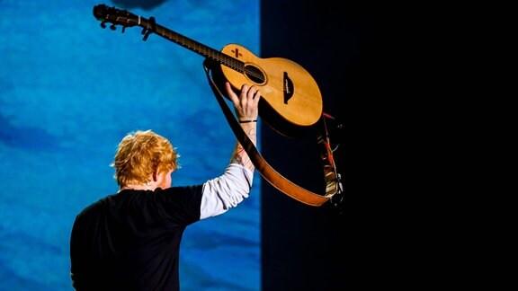 Ed Sheeran hält Gitarre hoch