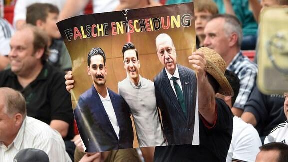 Ein Mann mit einem Bild des umstrittenen Besuch Özils und Gündogans beim türkischen Ministerpräsidenten Erdogan