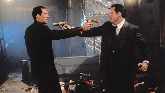 Nicolas Cage und John Travolta stehen sich mit gezogenen Waffen gegenüber. Szene aus dem Film ''Face Off''