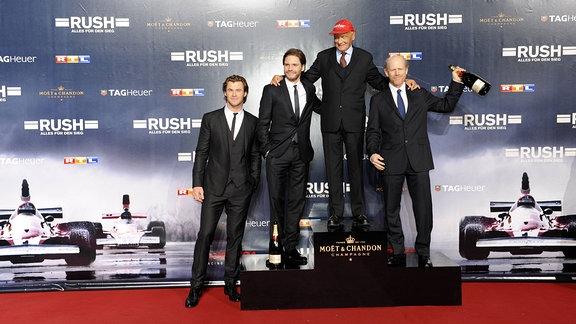 Die Schauspieler Chris Hemsworth, Daniel Brühl, Ex-Rennfahrer Niki Lauda und Regisseur Ron Howard (l-r) kommen am 28.09.2013 zur Deutschlandpremiere des Kinofilms Rush in Köln.