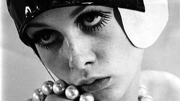 Eine Frau mit modischer Haube und Perlenkette posiert für ein Foto. Portraitaufnahme.
