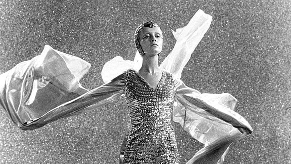 Filmszene - Eine Frau in engem Kostüm tanzt.