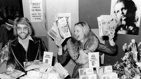 Zwei Personen sitzen hinter einem Verkaufsständ und lächeln.
