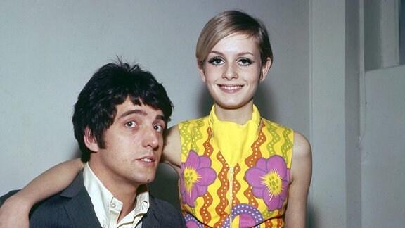 Eine Frau sitzt bei einem Mann auf dem Schoß. Beide posieren für ein Foto und lächeln in die Kamera.