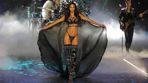 Model trägt Unterwäsche und Umhang