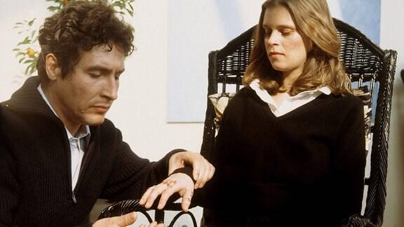 Ein Mann kniet vor einem Mädchen und untersucht ihre Hand.