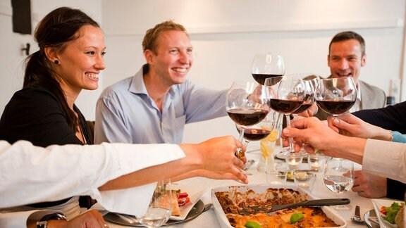 Menschen stoßen an einem Tisch mit Weingläsern an.