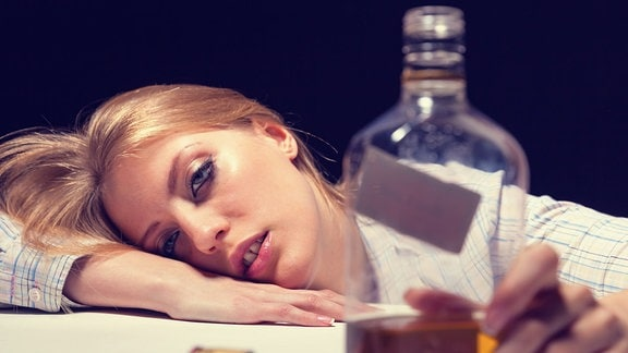 Eine Frau liegt neben einer Flasche mit dem Kopf auf dem Tisch.