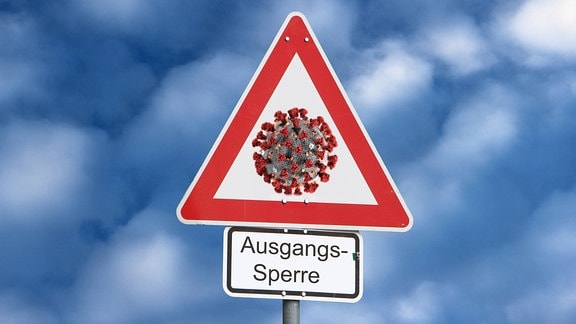 Verkehrsschild Achtung Gefahr mit Virus und Zusatz Ausgangssperre vor wolkigem Himmel