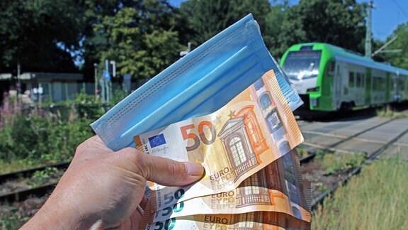 Maske und Geldscheine werden in einer Hand gehalten, im Hintergrund eine grüne Regionalbahn.