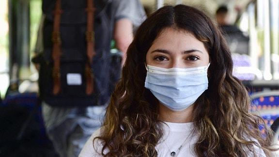 Schülerin trägt einen Mund-Nasen-Schutz im Schulbus.