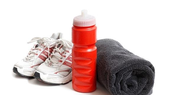 Sportschuhe stehen neben einer Trinkflasche und einem zusammengerolltem Handtuch.