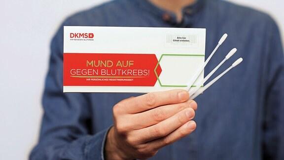 Ein Mann hält eine Karte des DKMS - Mund auf gegen Blutkrebs - und Teststäbchen in die Kamera.