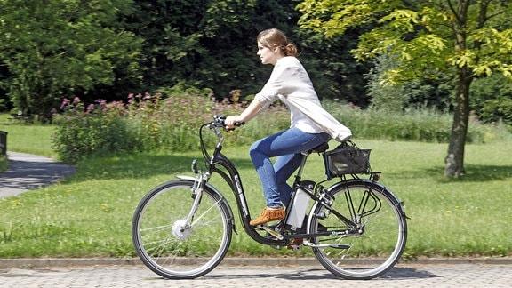 Eine Frau fährt mit einem Elektrofahrrad e-bike citystar mit austauschbarem Lithium-Ionen-Akku