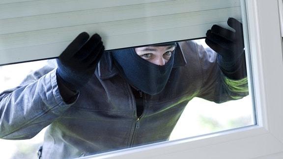Maskierter Mann hebt Rollladen an und sieht durch ein Fenster