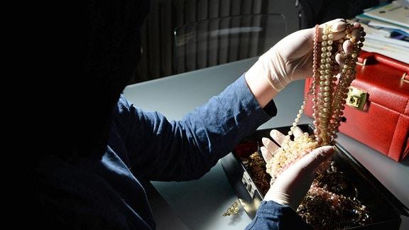 Einbrecher begutachtet eine Schatulle mit Schmuck