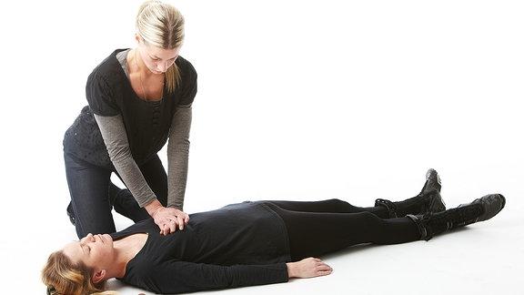 Eine junge Frau macht bei einer anderen Frau eine Herzdruckmassage