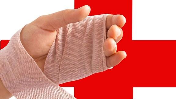 Eine verbundene Hand vor einem roten Kreuz