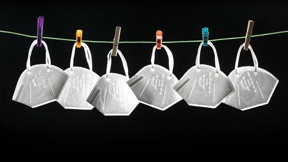 Auf einer Wäscheleine hängen vor schwarzem Hintergrund 6 Stück FFP2-Einweg-Masken.