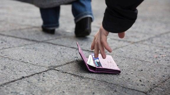 Ein Mann hebt eine Geldbörse vom Fußeg auf.