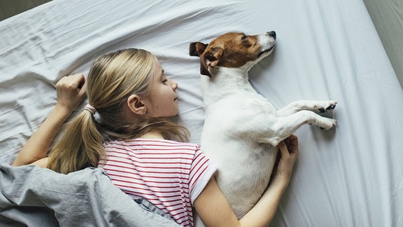 Ein Blondes Mädchen liegt mti einem Hund auf einem Bett
