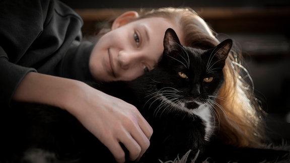 Ein Mädchen schmust mit einer schwarzen Katze