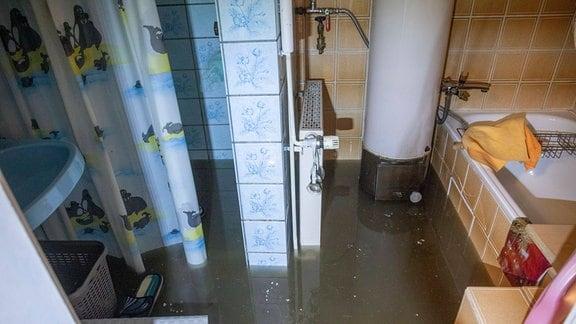 Ein Badezimmer ist mit schmutzigem Wasser überflutet.