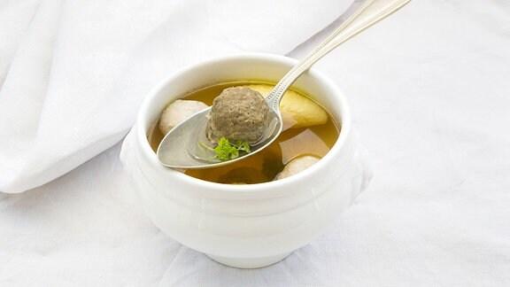Eine Suppenschüssel mit Löffel steht auf einem Tisch mit weißer Tischdecke.