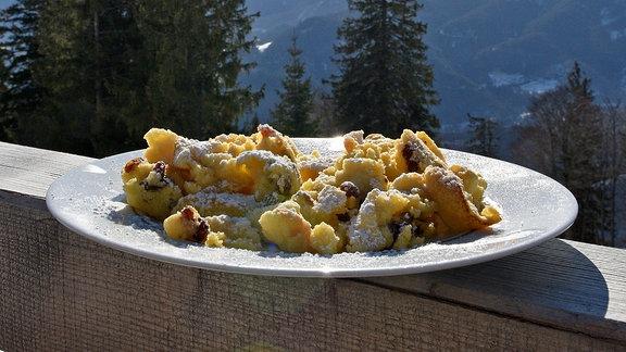 Ein Teller mit Kaiserschmarrn auf einer Brüstung, dahinter eine Berglandschaft