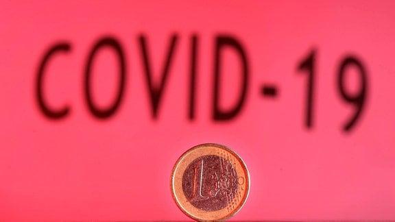 Symbolbild - Eine Ein-Euro Münze vor Schriftzug Covid-19.