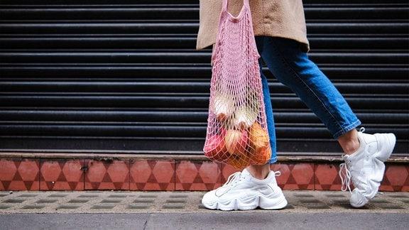 Frau mit Früchten in Tragenetz auf Fußweg.