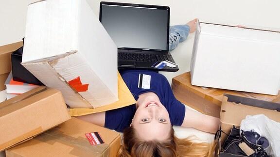 Frau mit Kartons und Laptop.