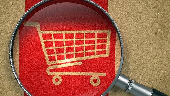 Symbol Einkaufswagen unter Vergrößerungsglas.