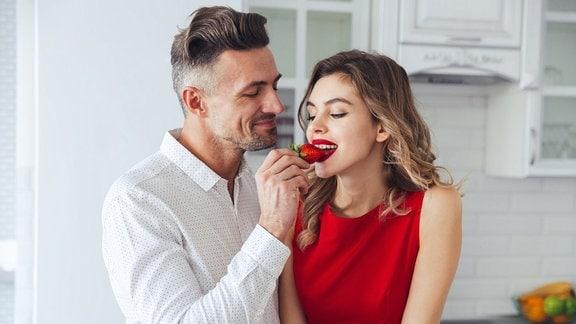 Junge Frau beißt in eine Erdbeere, die ein Mann ihr hinhält