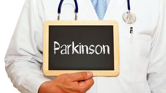 Illustration: Ein Arzt hält eine Tafel mit der Aufschrift «Parkinson».