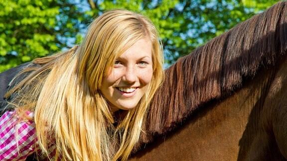 Junge Frau sitzt auf einem Pferd.