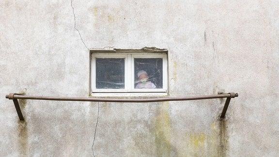 Eine Puppe sitzt hinter einem Fenster.