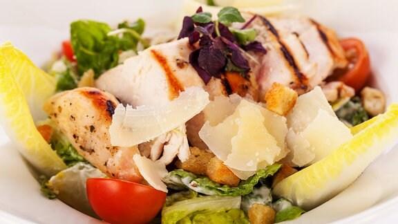 Frischer, leckerer Caesarsalat mit gegrillter Hähnchenbust, Parmesansplittern und Croutons.