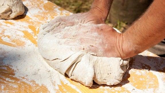 Männerhände kneten Teig