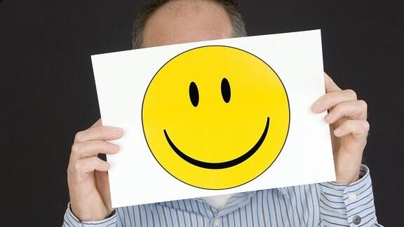 Mann hält sich einen Smiley vor das Gesicht