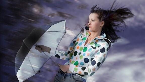Junge Frau hält Regenschirm gegen den Wind