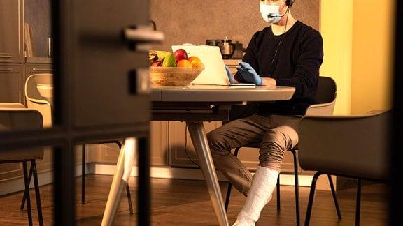 Ein Mann mit Gipsbein sitzt an einem Tisch vor einem Laptop
