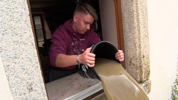 Eine Person schüttet Wasser aus einem Fenster.