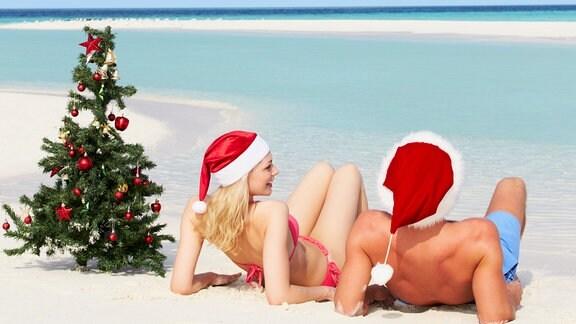 Ein Paar sitzt mit aufgesetzten Weihnachtsmützen neben einem Weihnachtsbaum am Strand.