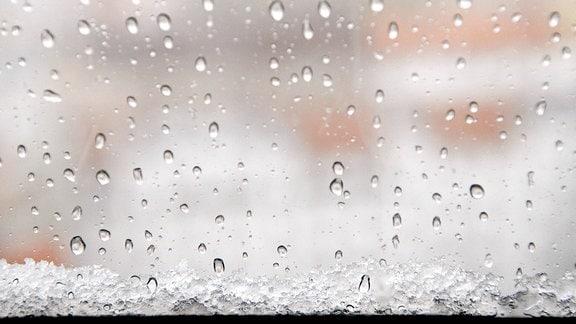 Schneeregen und Hagel zeigt sich in Tropfen und Schneematsch an einer Fensterscheibe