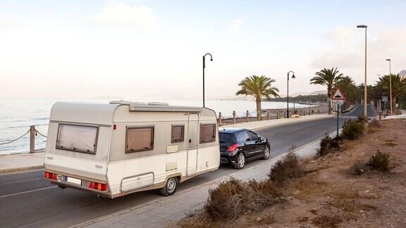 Pkw mit Wohnwagen fährt auf einer Straße am Meer