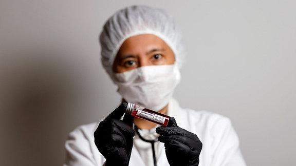 Eine Virologin posiert mit einer Corona-Blutprobe Symbolto mit Model.