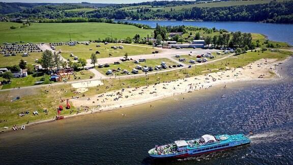 Ein Schiff vor einem Strand mit Campingplatz