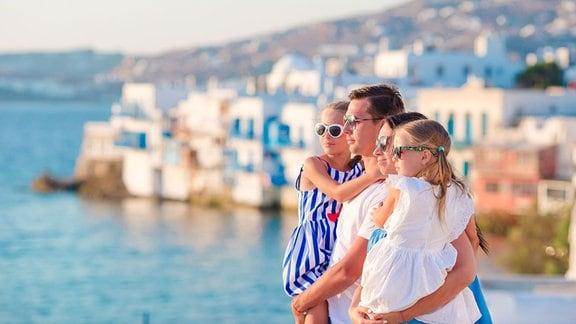 Eine Familie blickt im Sonnenschein auf das Meer