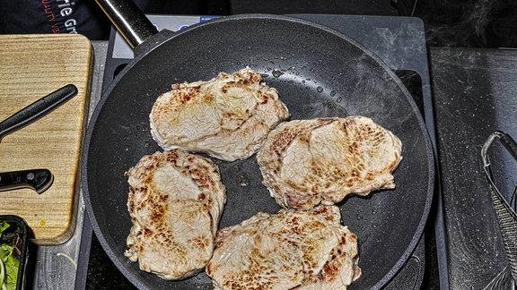 Fleisch wird in einer Pfanne gebraten.
